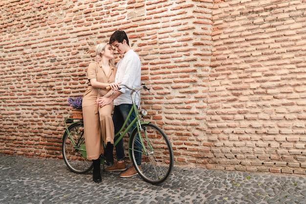 Romantisches paar, das draußen mit einem fahrrad aufwirft