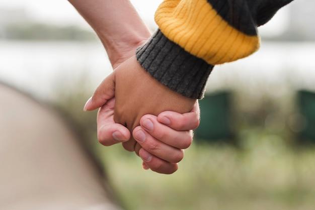 Romantisches paar, das hände im freien hält
