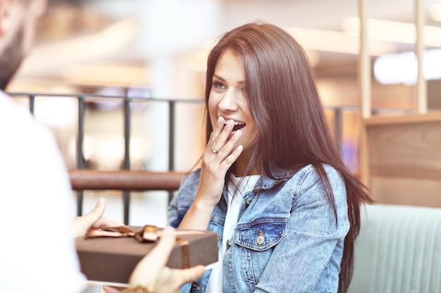 Romantisches paar, das im café verabredet und geschenke hält