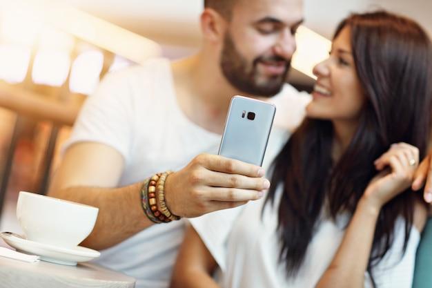Romantisches paar, das im café verabredet und selfie macht