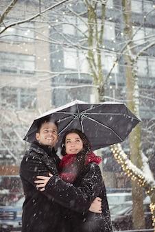 Romantisches paar, das in der straße während des schneefalls umarmt