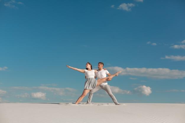 Romantisches paar, das in sandwüste am blauen himmelhintergrund tanzt.