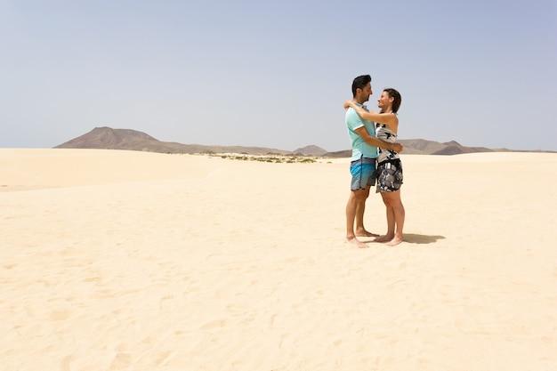 Romantisches paar, das sich auf leerer wüste im corralejo naturpark ansieht. mann und frau, die auf sanddünen in fuerteventura insel, spanien aufwerfen. sommertourismus, ikonische reisezielkonzepte