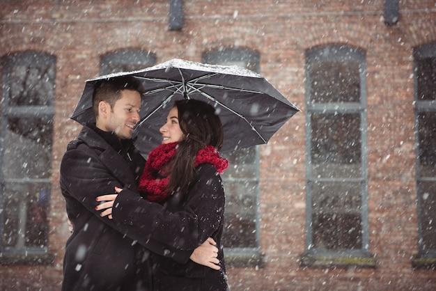 Romantisches paar, das während des schneefalls umarmt