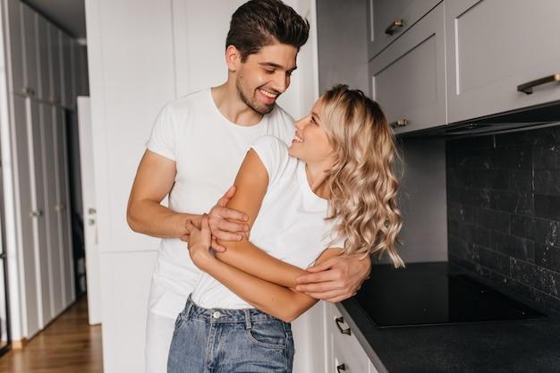 Romantisches paar, das zusammen mit aufrichtigem lächeln tanzt. innenporträt der glücklichen familie, die in der küche aufwirft.