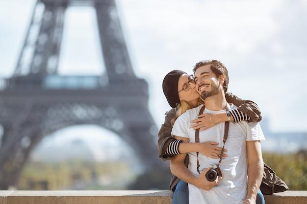 Romantisches paar des pariser eiffelturms, das küssen vor eiffelturm, paris, frankreich umarmt.