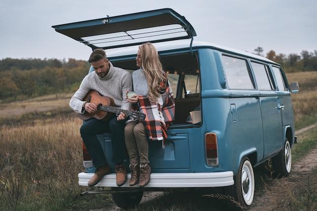Romantisches paar. hübscher junger mann, der gitarre für seine schöne freundin spielt, während er im kofferraum des blauen minivans im retro-stil sitzt