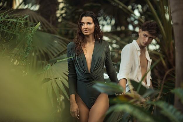Romantisches paar im tropischen dschungel, der zwischen exotischen pflanzen geht. junges attraktives schlankes mädchen