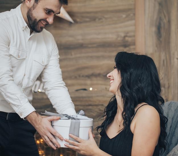 Romantisches paar in einem pullover mit geschenkbox