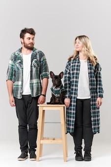 Romantisches paar in freizeitkleidung hat spaß mit ihrer französischen bulldogge auf weißer wand
