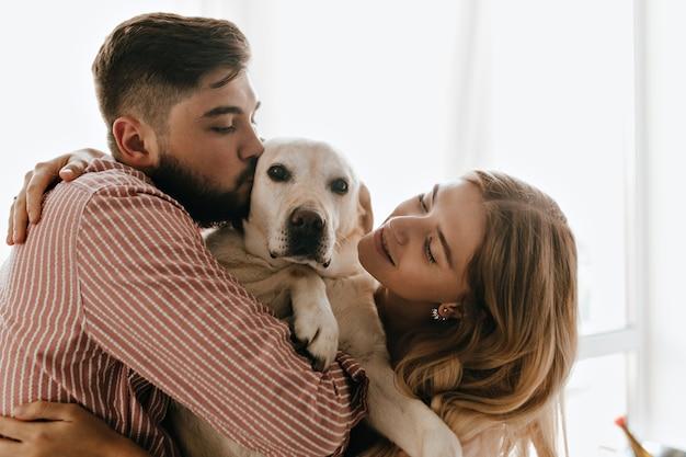 Romantisches paar in guter laune spielt und umarmt weißen hund. mann küsst seinen labrador gegen fenster.