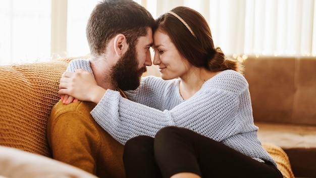 Romantisches paar mit mittlerem schuss auf der couch