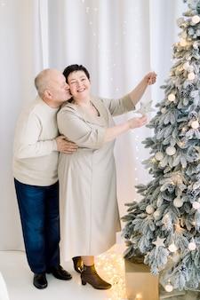 Romantisches paar mittleren alters, das weihnachtsbaum verziert