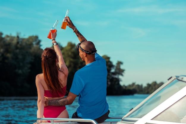 Romantisches paar. moderne junge leute, die flaschen mit alkoholfreien getränken halten, während sie auf dem deck eines vergnügungsbootes sitzen