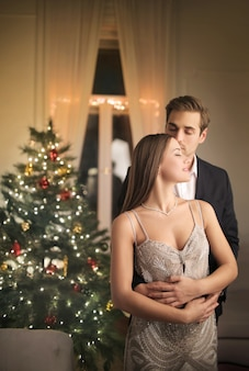 Romantisches paar, verkleiden sich mit eleganten kleidern, um die weihnachtsnacht zu feiern