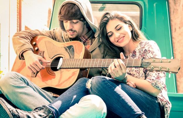 Romantisches paar von liebhabern, die gitarre auf altmodischem miniauto spielen