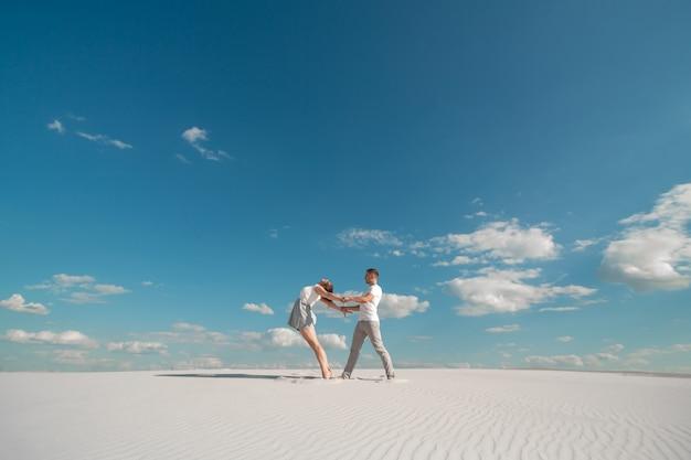 Romantisches paartanzen in der sandwüste am blauen himmel