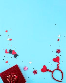 Romantisches partykonzept zum valentinstag. geschenkboxen, herzförmiges stirnband, süßigkeiten auf blauem hintergrund. draufsicht, flache lage, kopierraum