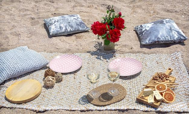 Romantisches picknick am sandstrand mit champagner, snacks und blumen. urlaubs- und romantikkonzept.