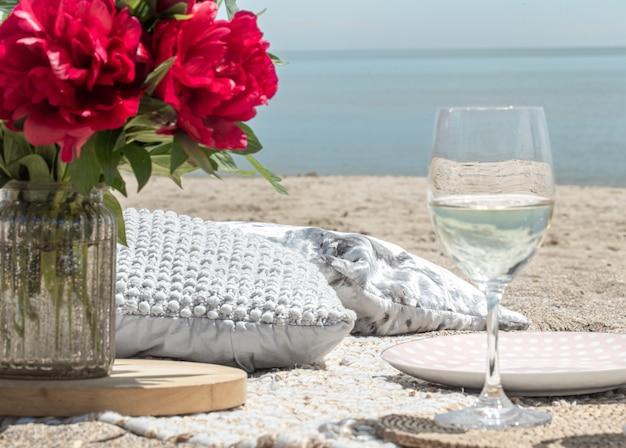 Romantisches picknick mit blumen und gläsern champagner am meer. das konzept eines urlaubs.