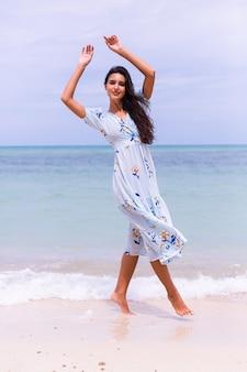 Romantisches porträt der frau im langen blauen kleid am strand durch meer am windigen tag
