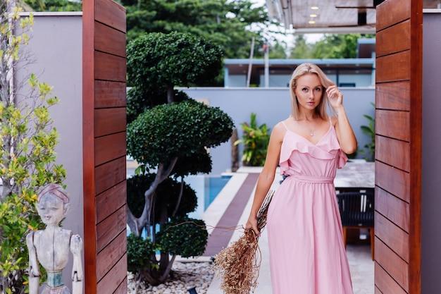 Romantisches porträt der frau im rosa abend süßes kleid halten wilde blumen außerhalb der tropischen luxusvilla schöne frau mit blumenstrauß