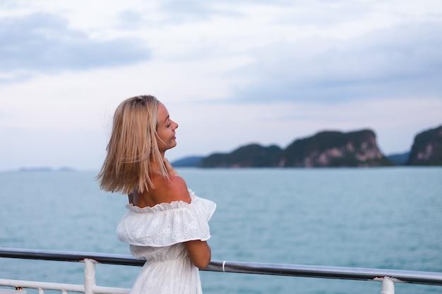 Romantisches porträt der frau im weißen kleid, das auf großer bootsfähre segelt
