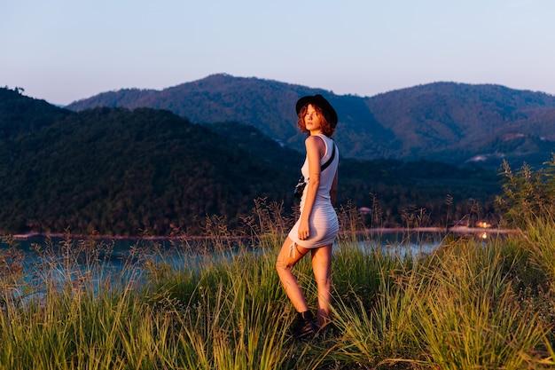 Romantisches porträt der jungen kaukasischen frau im sommerkleid, das das entspannen im park auf berg mit erstaunlichem tropischem meerblick genießt frau auf urlaubsreise durch thailand glückliche frau bei sonnenuntergang