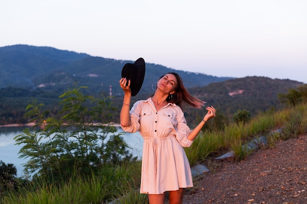 Romantisches porträt der jungen kaukasischen frau im sommerkleid, das das entspannen im park auf berg mit erstaunlichem tropischem meerblick genießt