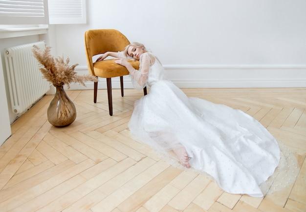 Romantisches porträt einer frau auf dem boden in einem schönen langen weißen kleid. das mädchen ist blond mit blauen augen und wunderschönem make-up im gesicht.