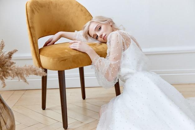 Romantisches porträt einer frau auf dem boden in einem schönen langen weißen kleid.