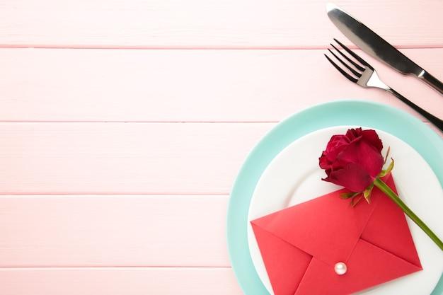 Romantisches restaurant tischdekoration mit roter rose auf tellern. valentinstag