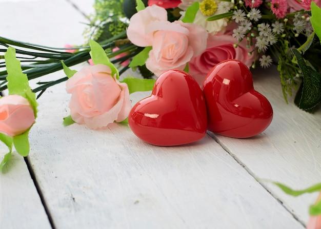 Romantisches rotes herz des valentinstags und bunter blumenstrauß auf weißem holztisch
