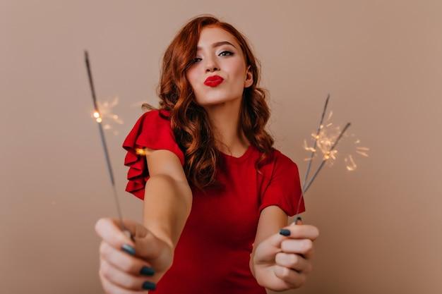 Romantisches rothaariges mädchen, das bengalische lichter auf neujahrsparty hält. ansprechendes weibliches modell mit wunderkerzen, die weihnachten feiern.