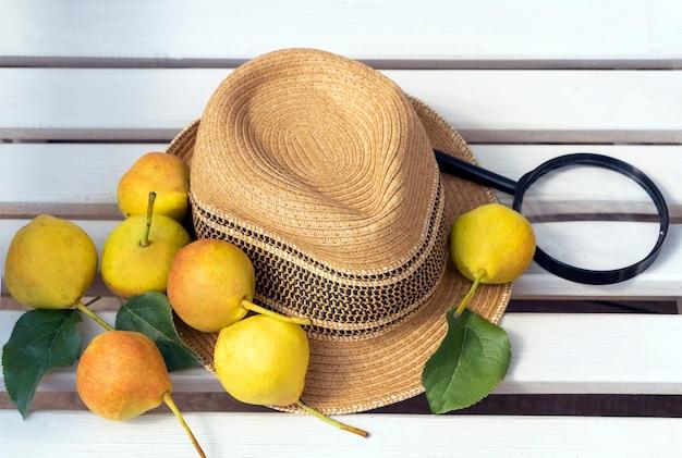 Romantisches rustikales stillleben mit hüten und reifen bio-birnen. herbst - sommergartenkomposition. ernte. shabby-chic-stil