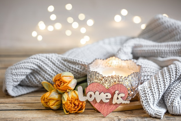 Romantisches stillleben mit brennender kerze, dekor, frischen blumen und gestricktem element