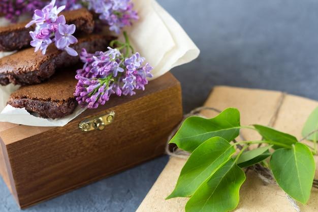 Romantisches stillleben mit lila blumen und brownie, nassem kuchen. dessert für tee- oder kaffeepause in holzkiste serviert. snack an einem frühlingstag im garten.