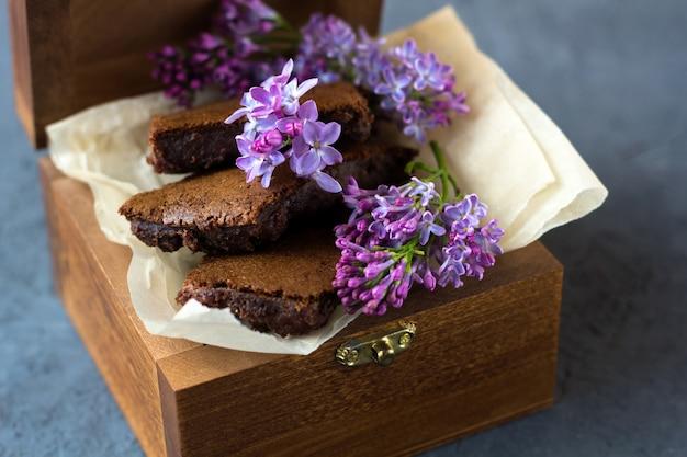 Romantisches stillleben mit lila blumen und brownie, nassem kuchen. dessert zum servieren mit tee- oder kaffeepause in holzkiste. snack an einem frühlingstag im garten.