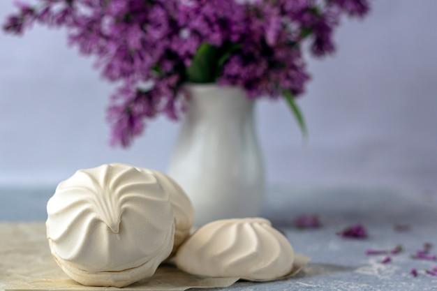 Romantisches stillleben mit lila blumen und marshmallows. snack an einem frühlingstag im garten. dessert zum servieren mit tee- oder kaffeepause.