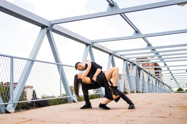 Romantisches tangotanzenpaar, das an der brücke durchführt