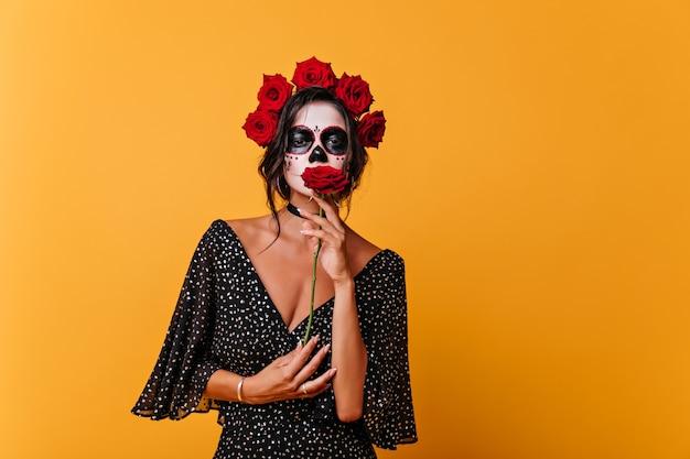 Romantisches totes mädchen im schwarzen kleid, das rote rose hält. innenporträt des weiblichen zombies trägt blumenkranz.