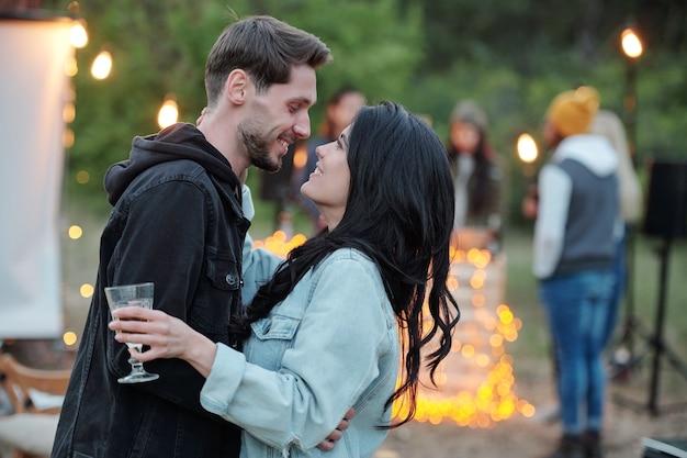 Romantisches und liebevolles junges paar in freizeitkleidung, das sich vor der kamera auf hintergrund ihrer freunde ansieht