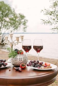 Romantisches valentinstagsessen am strand: zwei gläser rotwein, frisches obst und ein kerzenständer auf einem holztisch