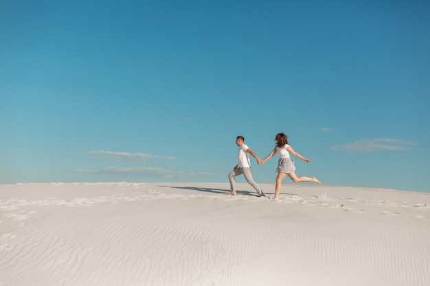 Romantisches verliebtes paar, das auf weißem sand in der wüste läuft.