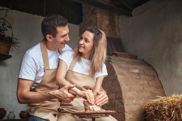 Romantisches verliebtes paar, das zusammen an töpferscheibe und scu arbeitet