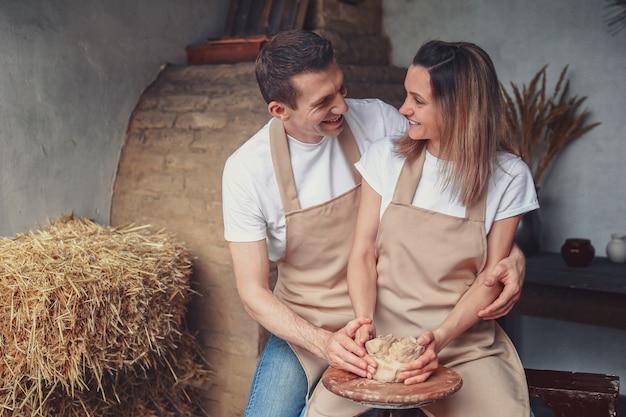 Romantisches verliebtes paar, das zusammen auf töpferscheibe arbeitet und tontopf modelliert