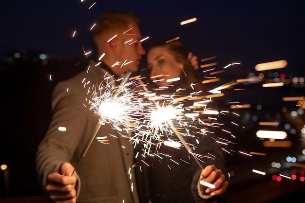 Romantisches verliebtes paar feiert gemeinsam den neujahrsstart oder das event-party-nachtleben mit feuerwunderkerze.