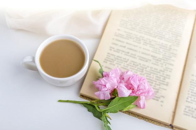 Romantisches vintage stillleben mit rosa blumen, altem buch, tasse tee oder kaffee im frühling, sommertag im garten