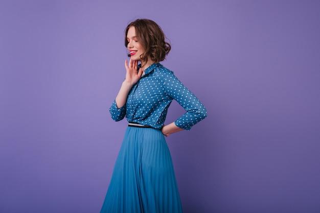 Romantisches weibliches modell mit inspiriertem gesichtsausdruck, der auf lila wand aufwirft. foto der scherzhaften kurzhaarigen frau trägt eleganten langen rock.