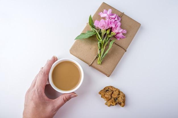 Romantisches weinlesestillleben mit hübscher geschenkbox, die mit braunem bastelpapier eingewickelt und mit rosa blume auf weißem hintergrund verziert wird